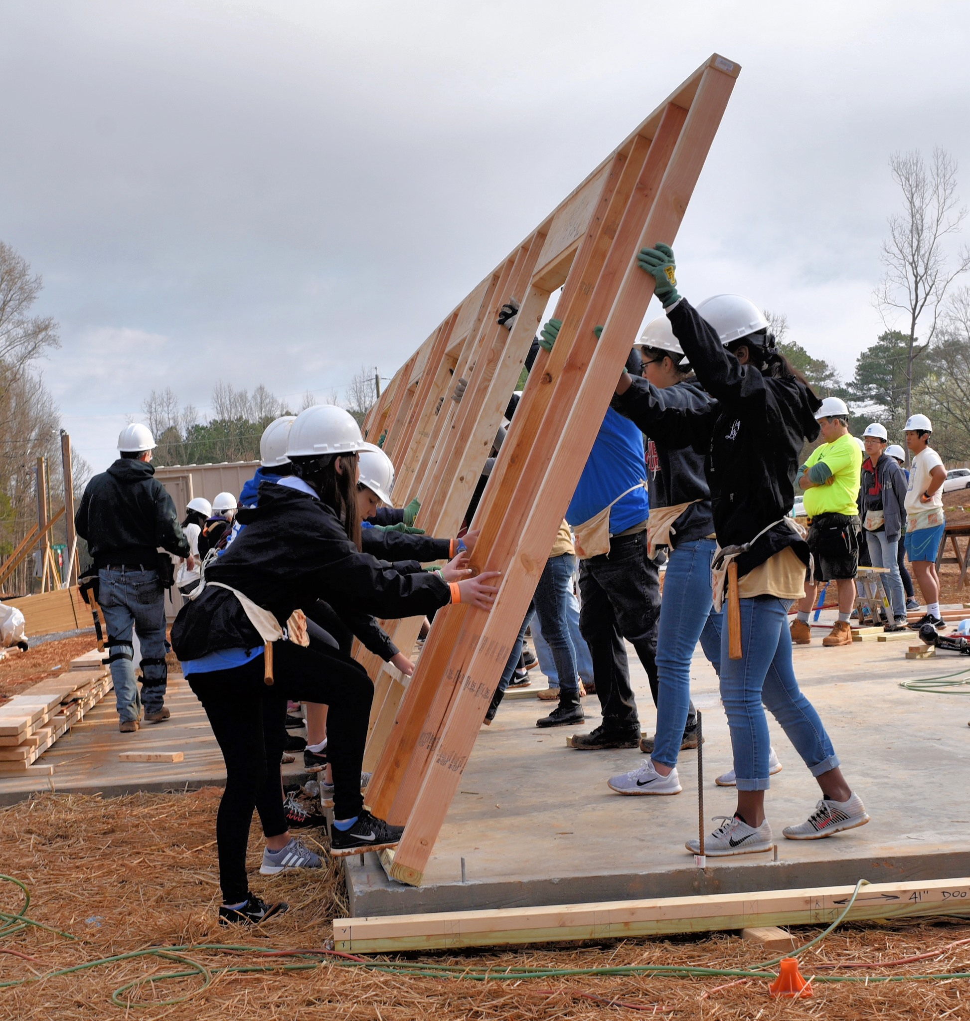 People raising a wooden beam up